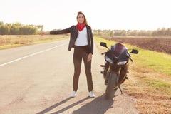 Pełny długość strzał piękny kobieta rowerzysta problemy z rowerem na drodze, hitchhikes kierowców i pyta dla pomocy, ubierającej  zdjęcie stock