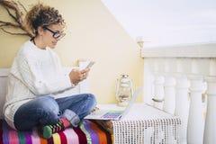 Pełny koloru wizerunek dla wiek średni kobiety pracującej wolności przy laptopem plenerowym w tarasie, stara rocznik lampa w tle  obrazy stock