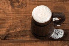 Pełny kubek świeży piwo na drewnianym stole. zdjęcie stock