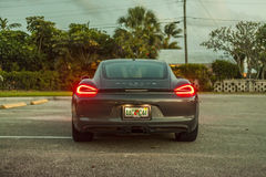 Pełny strzału plecy widok Porsche Cayman z plecy zaświeca dalej Nig Zdjęcia Stock