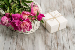 Peônias bonitas das flores na cesta com a caixa de presente no fundo de madeira claro Fotos de Stock Royalty Free