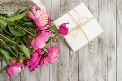 Peônias bonitas das flores na cesta com a caixa de presente no fundo de madeira claro Vista superior Fotografia de Stock Royalty Free