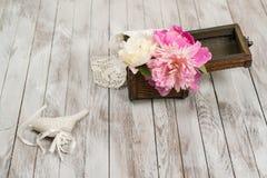 Peônias bonitas das flores na cesta e na decoração no fundo de madeira claro Fotos de Stock Royalty Free