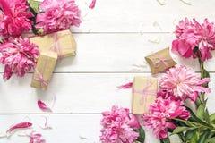Peônias cor-de-rosa com as caixas de presente no fundo de madeira branco lugar Imagens de Stock