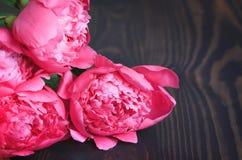 Peônias cor-de-rosa em uma tabela de madeira Fundo floral bonito do fundo… com flores coloridas Imagem de Stock Royalty Free