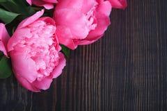 Peônias cor-de-rosa em uma tabela de madeira Fundo floral bonito do fundo… com flores coloridas Imagens de Stock Royalty Free