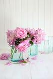 Peônias cor-de-rosa nos frascos de vidro fotografia de stock