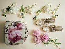 Peônias luxúrias com botões, sandálias e bolsa em um fundo branco Fotos de Stock