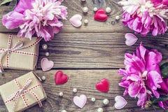 Peônias roxas com caixas de presente, corações e pérolas em de madeira velho Imagens de Stock Royalty Free