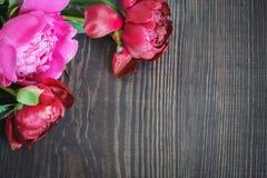 Peônias vermelhas e cor-de-rosa em uma tabela de madeira Fundo floral bonito do fundo… com flores coloridas Foto de Stock Royalty Free