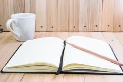 Põe o lápis sobre o caderno perto da xícara de café Foto de Stock