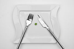 The pea. One pea on a white plate with fork and knife Stock Photos