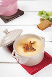Pea cream soup with bacon crisps in pots. On a white wooden background Royalty Free Stock Images