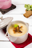 Pea cream soup with bacon crisps in pots. On a white wooden background Stock Photography