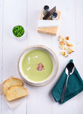 Pea cream soup with bacon in a white plate with toast. Green peas in a plate on a white table. Lunch at the restaurant Stock Images