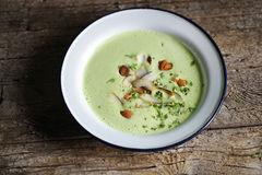 Pea cream soup with coconut, almonds and herbs Stock Photo