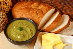 Pea and ham soup. Bowl of homemade pea and ham soup in kitchen setting surrounded by crusty bread and butter Royalty Free Stock Image