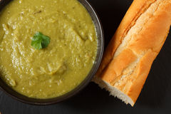 Pea and ham soup. Bowl of homemade pea and ham soup in with crusty french bread Royalty Free Stock Image