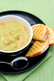 Pea and Ham Soup. A bowl of pea and ham soup, with fresh toasted sourdough bread Stock Photos