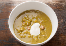 Pea and Ham soup. Delicious pea and ham soup with a don of cream in a white bowl on rustic wood setting Stock Images