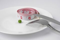 Pea and measuring tape on a plate Royalty Free Stock Images