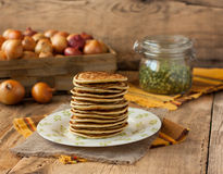 Pea pancakes with onion on a wooden table. Pea pancakes with onions on a plate on a wooden table with pea and sackcloth Stock Image