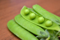 Pea pods on wooden table. Stock Photography