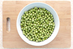 Pea seeds in bowl with chopping board Royalty Free Stock Image