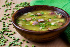 Pea soup. With smoked sausages in a wooden plate Royalty Free Stock Image