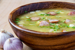 Pea soup. With smoked sausages in a wooden plate Royalty Free Stock Photography