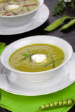 Pea soup. Bowls of pea soup with prosciutto garnished with chives. Sprig of flowering pea and cracked pea pods Royalty Free Stock Photography