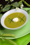Pea soup. Bowl of pea soup garnished with chives and cream. Sprig of flowering pea and cracked pea pods Stock Photography