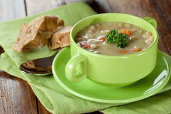 Pea soup with baguette. In a green bowl Stock Photo