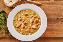 Pea Soup cremoso com a salsicha desbastada com pão Imagens de Stock Royalty Free