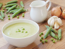 Pea soup and ingredients for cooking. Vegetable pea soup and ingredients for cooking. Peas, cream, onion and garlic. Wooden background. Close up view Stock Image