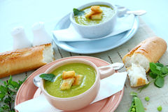 Pea Soup With mint. Delicious bowls of pea soup with fresh mint and crusty bread royalty free stock photo