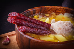 Pea soup with potatoes, pork ribs and pickled sausages in a wooden plate. Close-up stock image