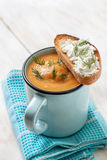 Pea soup puree in a blue mug. Toast with cream cheese on a white wooden background Stock Images