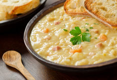 Pea Soup. A rustic bowl of hearty spit pea soup with smoked ham, carrots, potato, and french bread Royalty Free Stock Photo