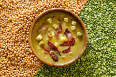 Pea soup with smoked products on a background of dried peas. Pea soup with smoked products in a wooden bowl. top view Stock Photo
