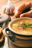 Pea soup with smoked sausage on brown wooden background. Stock Images