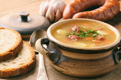 Pea soup with smoked sausage on brown wooden background. Stock Photo
