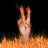 Peace. A hand rising out of flames holds two fingers out to demonstrate the peace sign.  The fingers and hand has flames to demonstrate the concept of Stock Photography