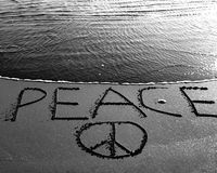 Peace. An ocean wave rushes to meet a message peace written in the sand. Photo in black and white royalty free stock image