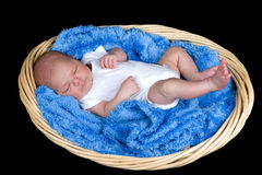 Peace. Beautiful baby boy sleeping in a basket on a blue blanket Royalty Free Stock Images