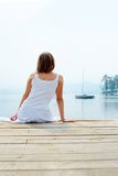 Peace. Rear view of pretty young lady in white cotton clothes having rest by the seaside royalty free stock image