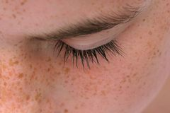 Peace. Eyelash detail  of a young girl with freckles Royalty Free Stock Image