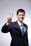 Peace. Attractive man in a suit shows a sign of peace on a gray background Stock Photography
