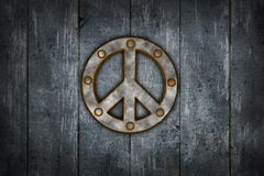 Peace. Rusted riveted pacific symbol on wooden background - 3d illustration Royalty Free Stock Image