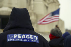 Peace. Back of person with peace sticker on his coat- blurred American flag flying in background Royalty Free Stock Photography